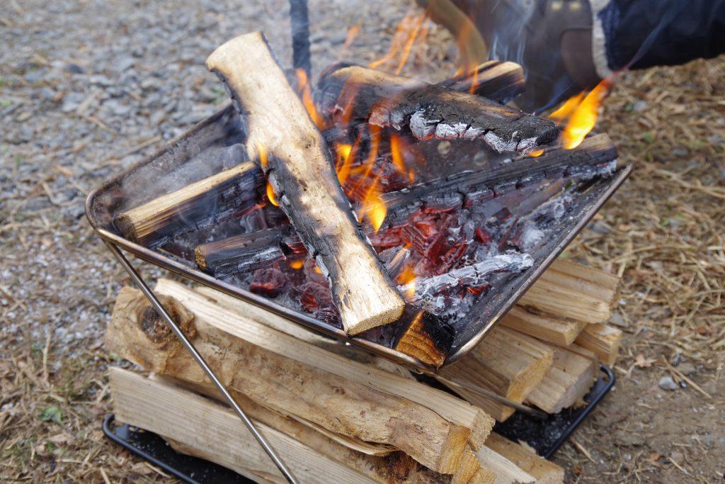 焚き火台の下で乾燥させている薪